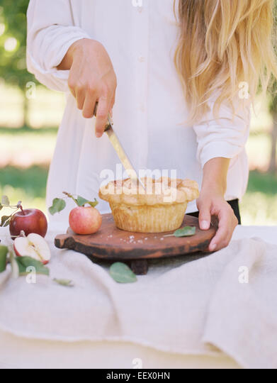 Woman standing at a table cutting an apple pie. - Stock Image