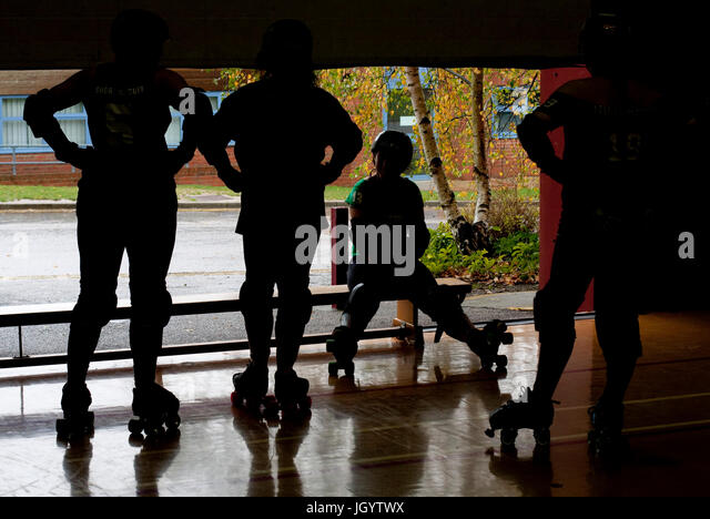 Roller derby skaters in silhouette - Stock Image