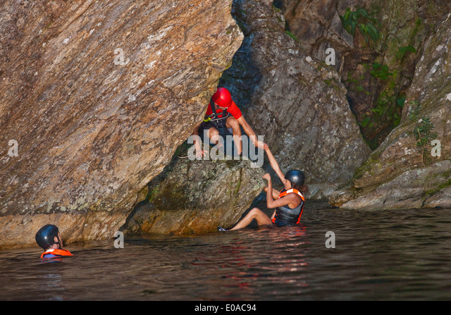 Men and woman canyoneering - Stock Image
