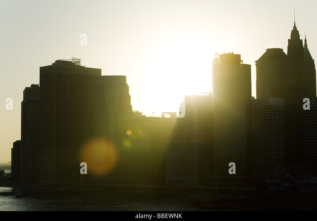 Silhouette of city skyline at sunset - Stock Image