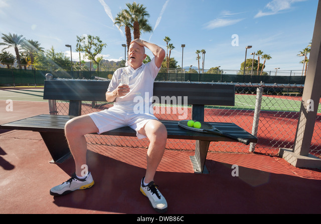 Tired senior tennis player relaxing on bench at court - Stock Image