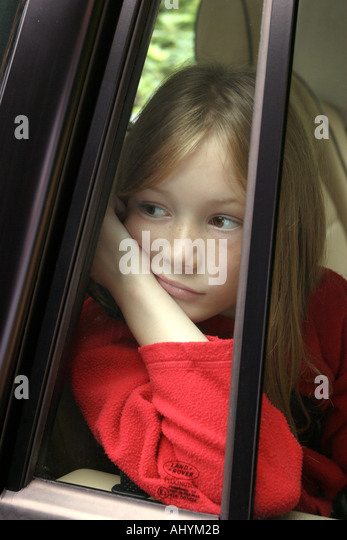 Bored, sad young car passenger gazes out of car window - Stock Image