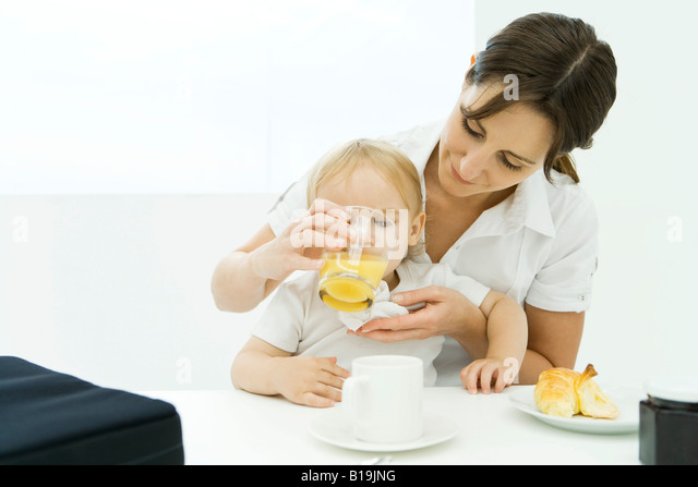 Woman helping baby drink from glass of juice - Stock-Bilder