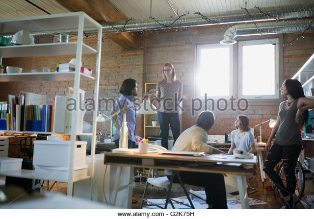 Designer standing on chair leading meeting in office - Stock Image