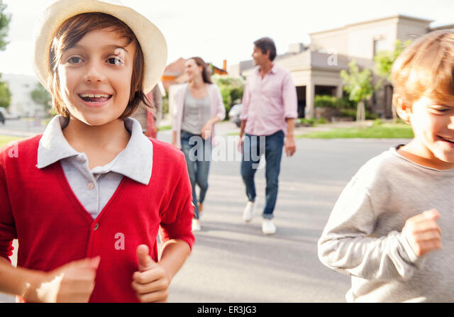 Boys running in street, family walking behind them - Stock Image