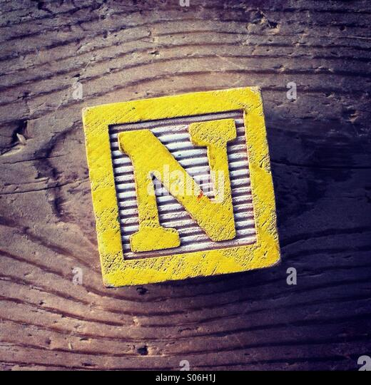 It's a woodblock toy with an alphabet letter on it: N - Stock Image