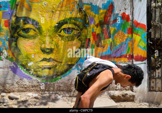 Peru Lima Barranco Bajada de los Banos street scene pedestrian sidewalk Hispanic man hunched over skinny carrying - Stock Image