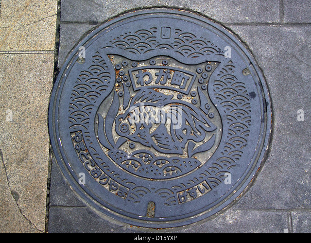manhole cover with its goldfish emblem shows the significance of goldfish to the city of Yamatokōriyama, Nara Prefecture, - Stock Image