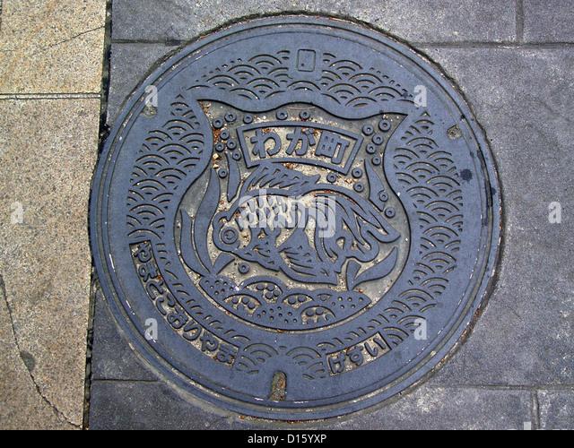 manhole cover with its goldfish emblem shows the significance of goldfish to the city of Yamatokōriyama, Nara Prefecture, - Stock Image