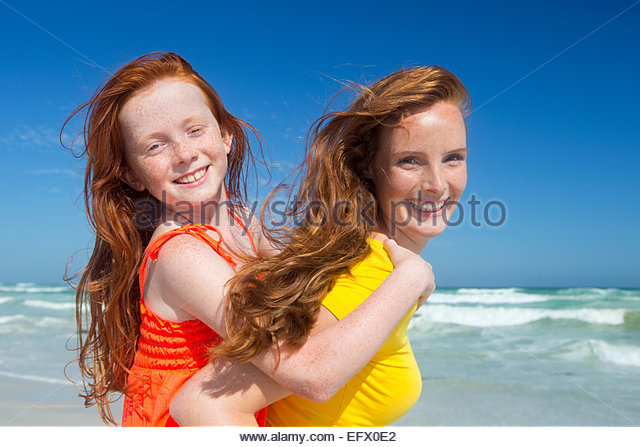 Smiling Mother giving daughter piggy-back on sunny beach - Stock Image