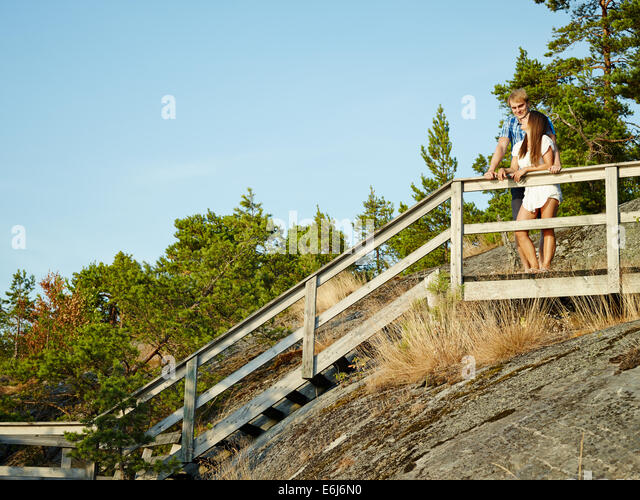 Young couple together on the fence, rocky and wooden environment - Stock-Bilder