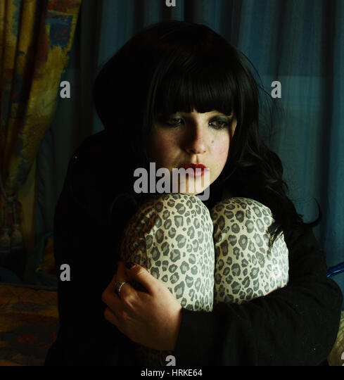 Sad young woman trapped in her bedroom - Stock Image