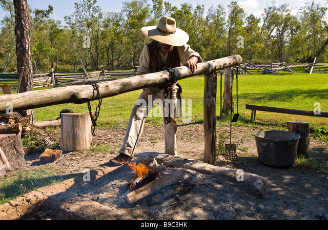 Settler working at open outdoor fire 1830s Jones Stock Farm George Ranch Historical Park Houston texas tx tourist - Stock Image