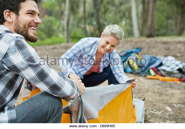 Happy mid adult man looking away while setting up tent with wife - Stock Image