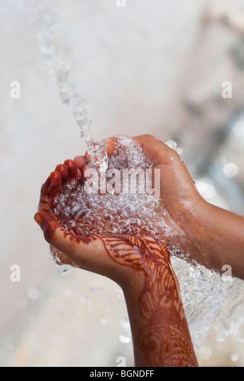Indian childs cupped hands catching poured water. India - Stock Image