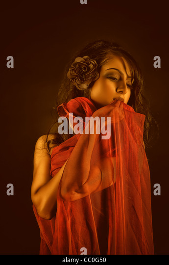 Beautiful woman covered with red fabric - Stock Image