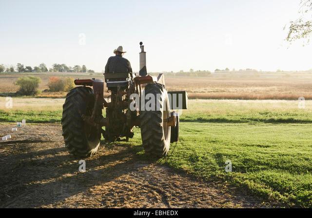 Rear view of senior male farmer driving tractor in field, Plattsburg, Missouri, USA - Stock Image