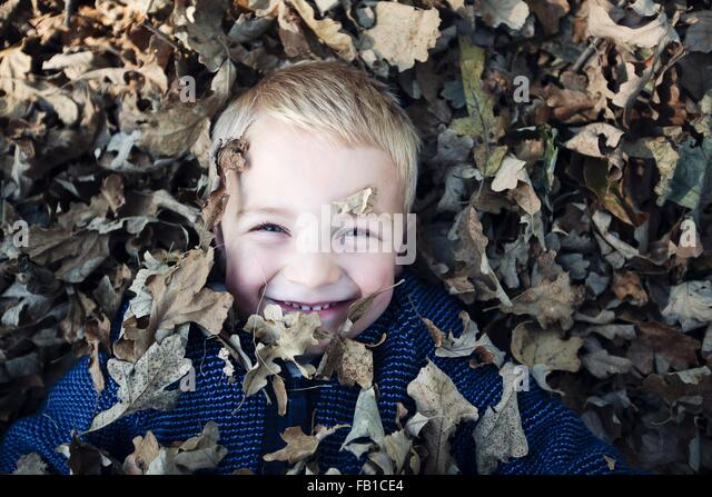 Overhead view of boy lying down covered in autumn leaves looking at camera smiling - Stock Image