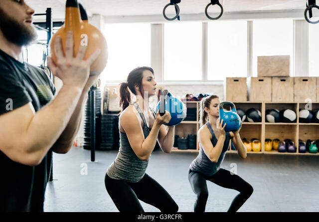 Germany, Young women and man cross training with kettlebells in gym - Stock Image