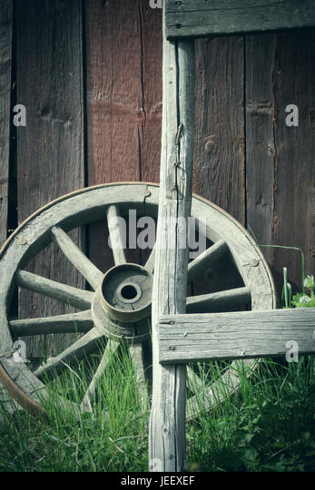 Old wagon wheel outside rural building wall. Rustic wooden nostalgia object. - Stock-Bilder