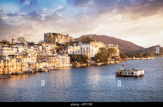 Lake Pichola with City Palace view at cloudy sunset sky in Udaipur, Rajasthan, India - Stock-Bilder