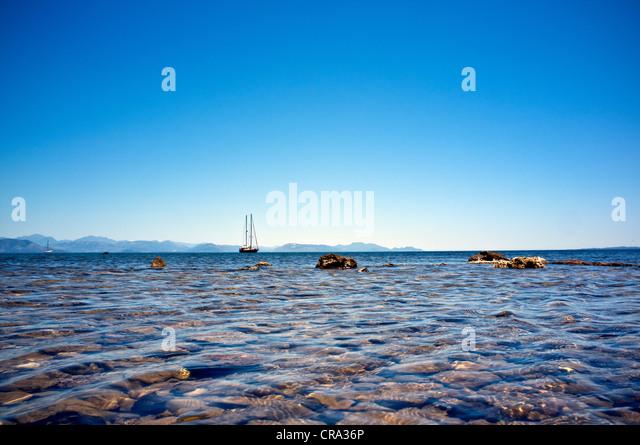 Yacht  on the horizon off of Corfu coast - Stock Image