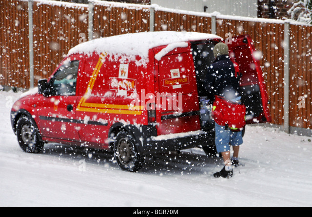 Royal Mail delivery van and postman in residential street during snow storm number plate obscured - Stock Image