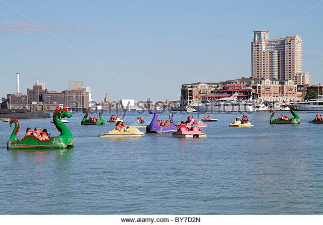 Maryland Baltimore Inner Harbor Patapsco River port waterfront Harborplace paddle boat ride dragon boat skyline - Stock Image