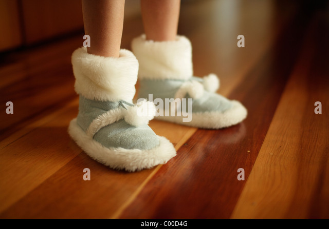 Girl's warm slippers on wooden floor made from synthetic sheepskin - Stock-Bilder