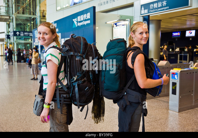 Two young women British backpackers at railway station in Hong Kong. JMH4157 - Stock Image