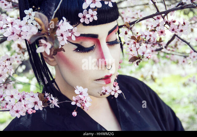 Portrait of a geisha in spring in a park full of almond trees - Stock Image