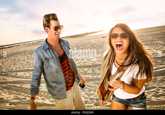 Young couple laughing on Mission Beach, San Diego, California, USA - Stock Image