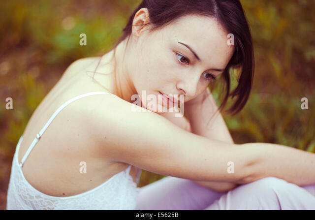 Young thoughtful woman sitting on a meadow - Stock Image