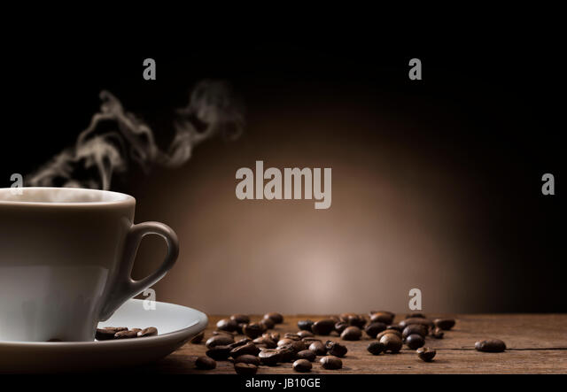 cup of steaming coffee on wooden table with roasted coffee beans. - Stock Image