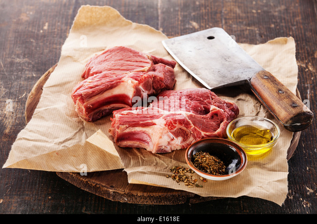 Raw fresh meat and meat cleaver on dark background - Stock Image