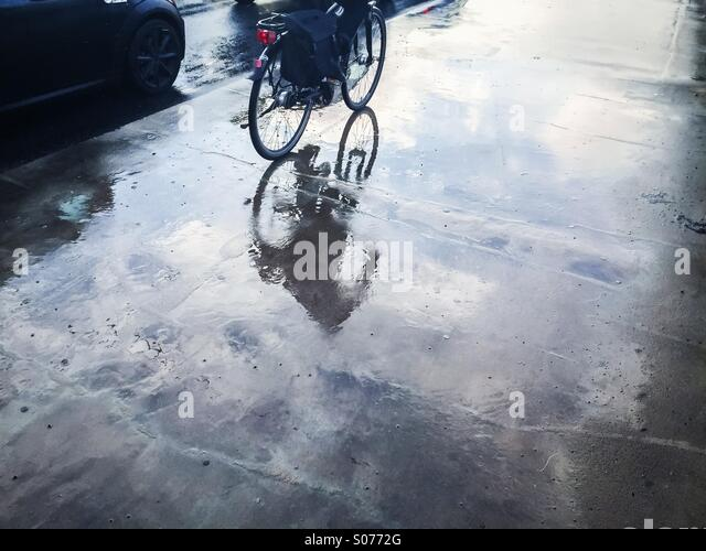 Cyclist on wet street with reflections - Stock Image