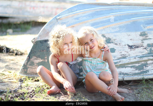 Portrait of two girls sitting by an upturned boat - Stock Image