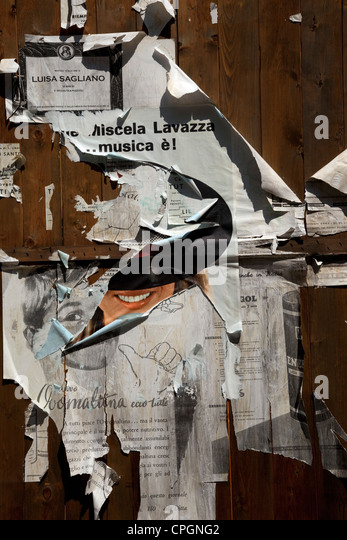 A collage of torn posters on a wall at the Cinecitta film studios in Rome, Italy. - Stock Image