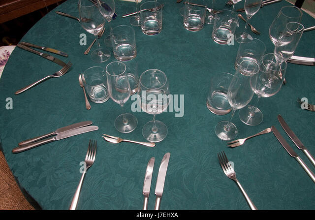 Glasses and cutlery laid on a dark green table cloth - Stock Image