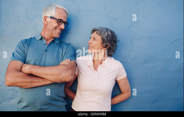 Portrait of affectionate mature couple looking at each other against blue background. Loving middle aged man and - Stock Image