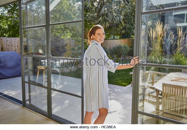 Mid adult woman standing at open door. - Stock Image