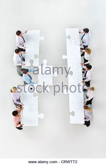 Business people standing face to face in rows and holding large jigsaw pieces - Stock Image