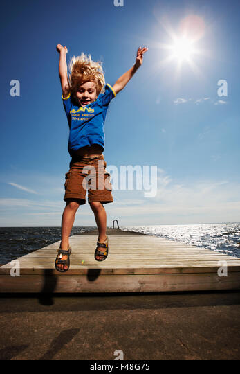 Boy on a jetty, Sweden. - Stock Image