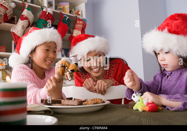 USA, California, Los Angeles, Mother with two daughters playing at Christmas morning - Stock Image