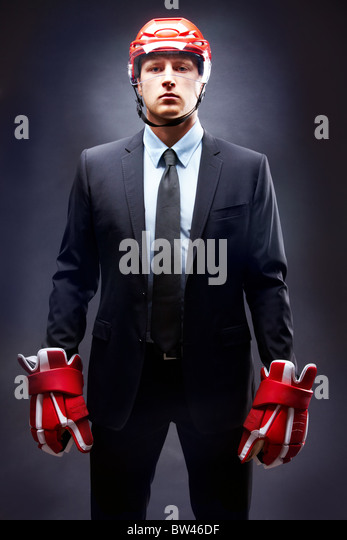 Portrait of young businessman in suit and hockey helmet and gloves - Stock Image