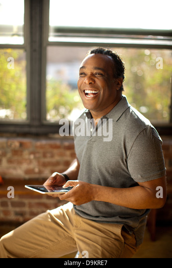 Man posing with charismatic smile holding digital tablet - Stock Image