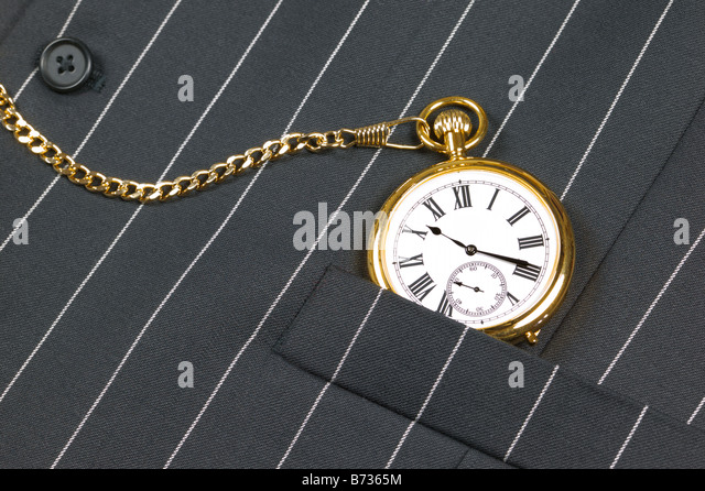 Gold pocket watch with roman numerals in the pocket of a waistcoat - Stock Image