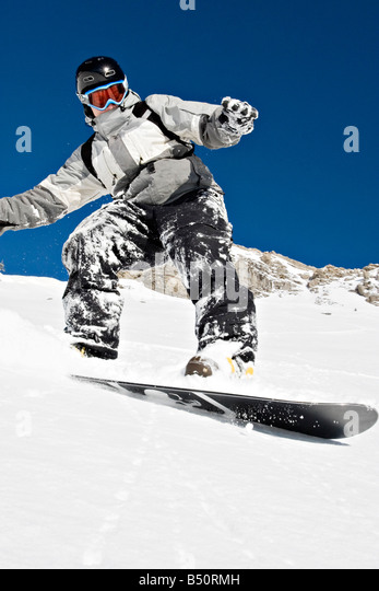 Low angle view of a young man snowboardingan Alps Switzerland - Stock Image
