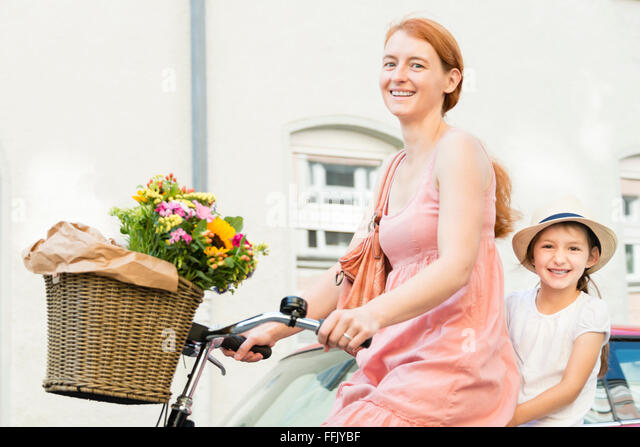 Mother and daughter cycling in city - Stock Image