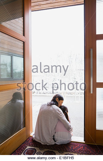 Mother and daughter hugging in doorway - Stock Image